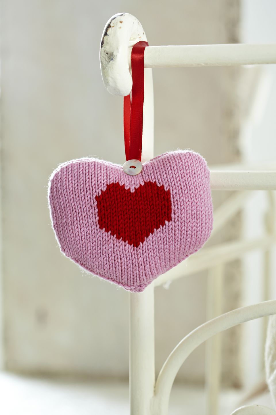 Knitted heart hanging by ribbon from bedstead, close-up