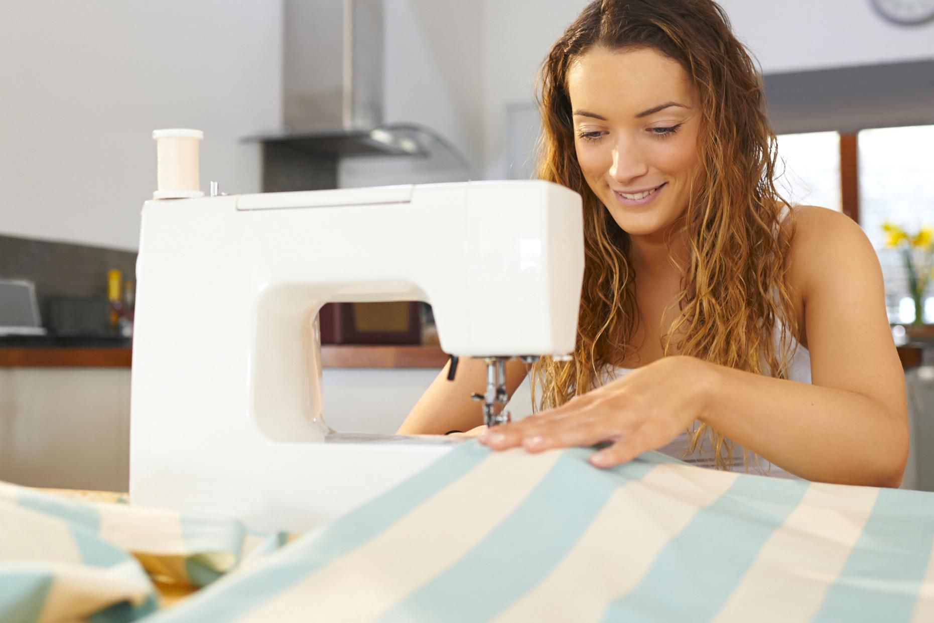 Woman using sewing machine at home.