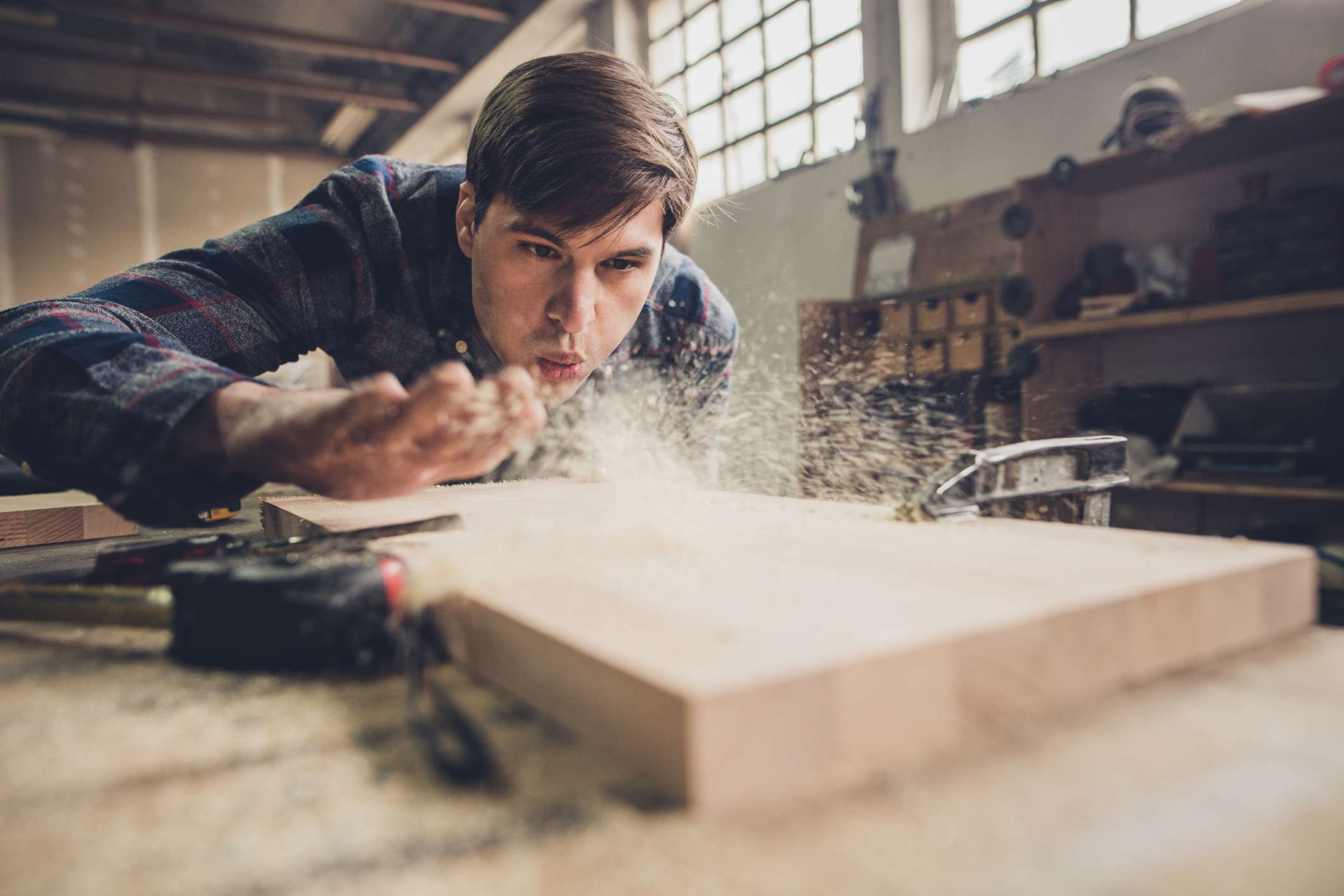 A carpenter blowing sawdust off a wooden board