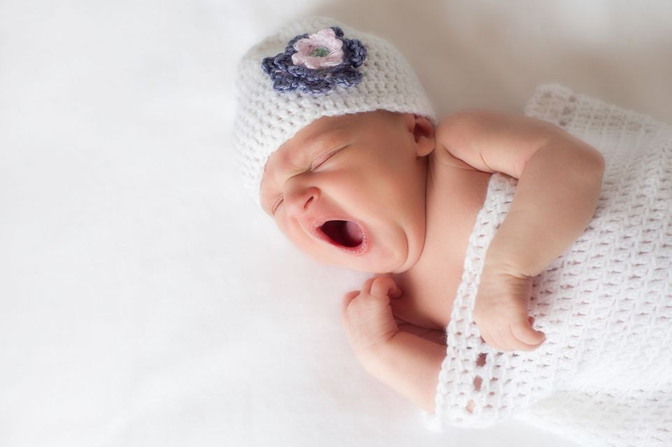 Newborn baby girl yawning in a crocheted outfit