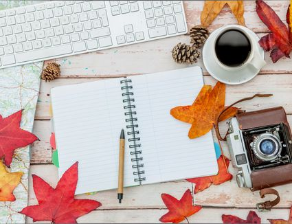 A desk with various fall leaves along with office supplies