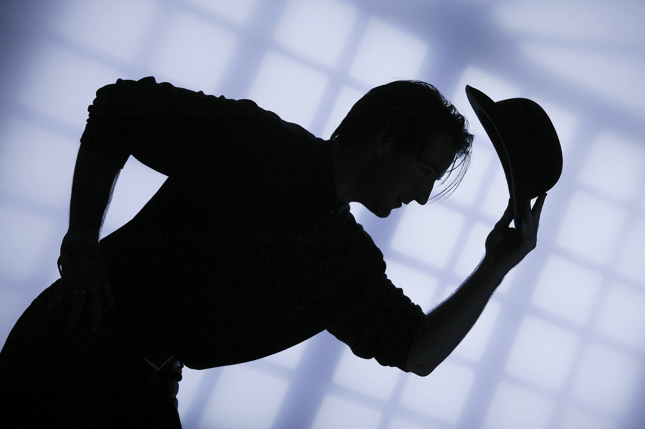 A shadow figure bowing, removing their hat