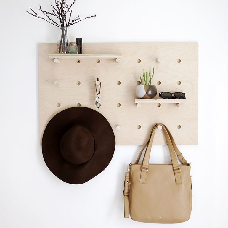 pegboard wall organizer with a hat, bag, and shelves on it.