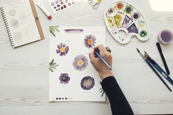 Woman painting flowers with water colors, top view