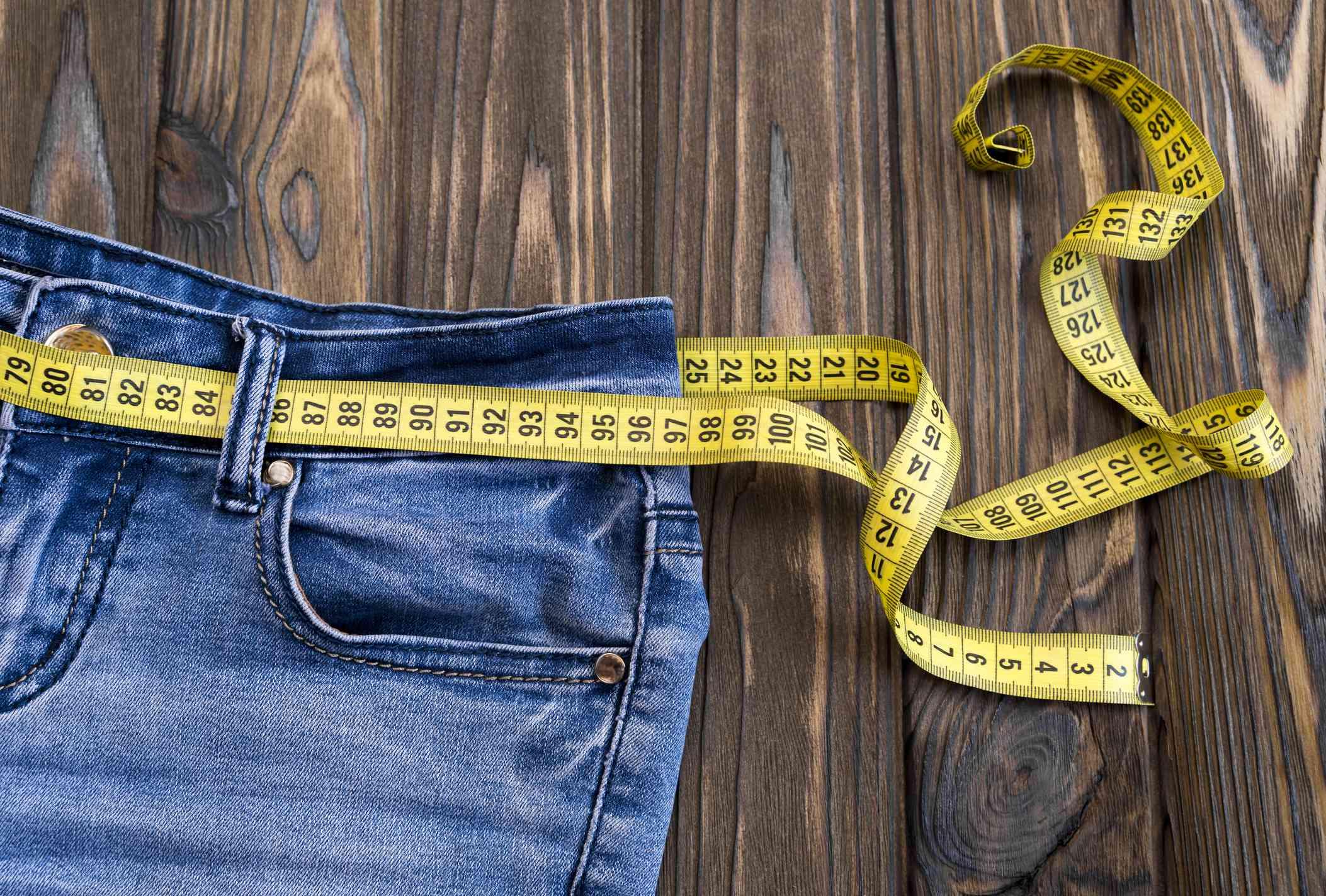 jeans, centimeter on a wooden background. diet. waist