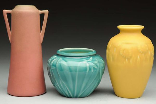 Three Rookwood vases in red, blue, and yellow.