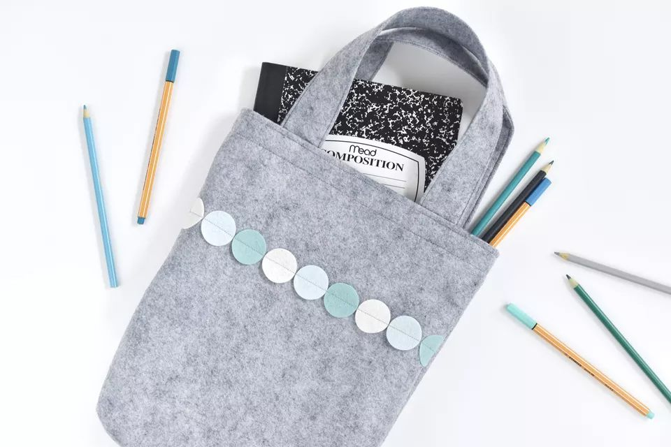 A gray felt bag with a notebook and pencils