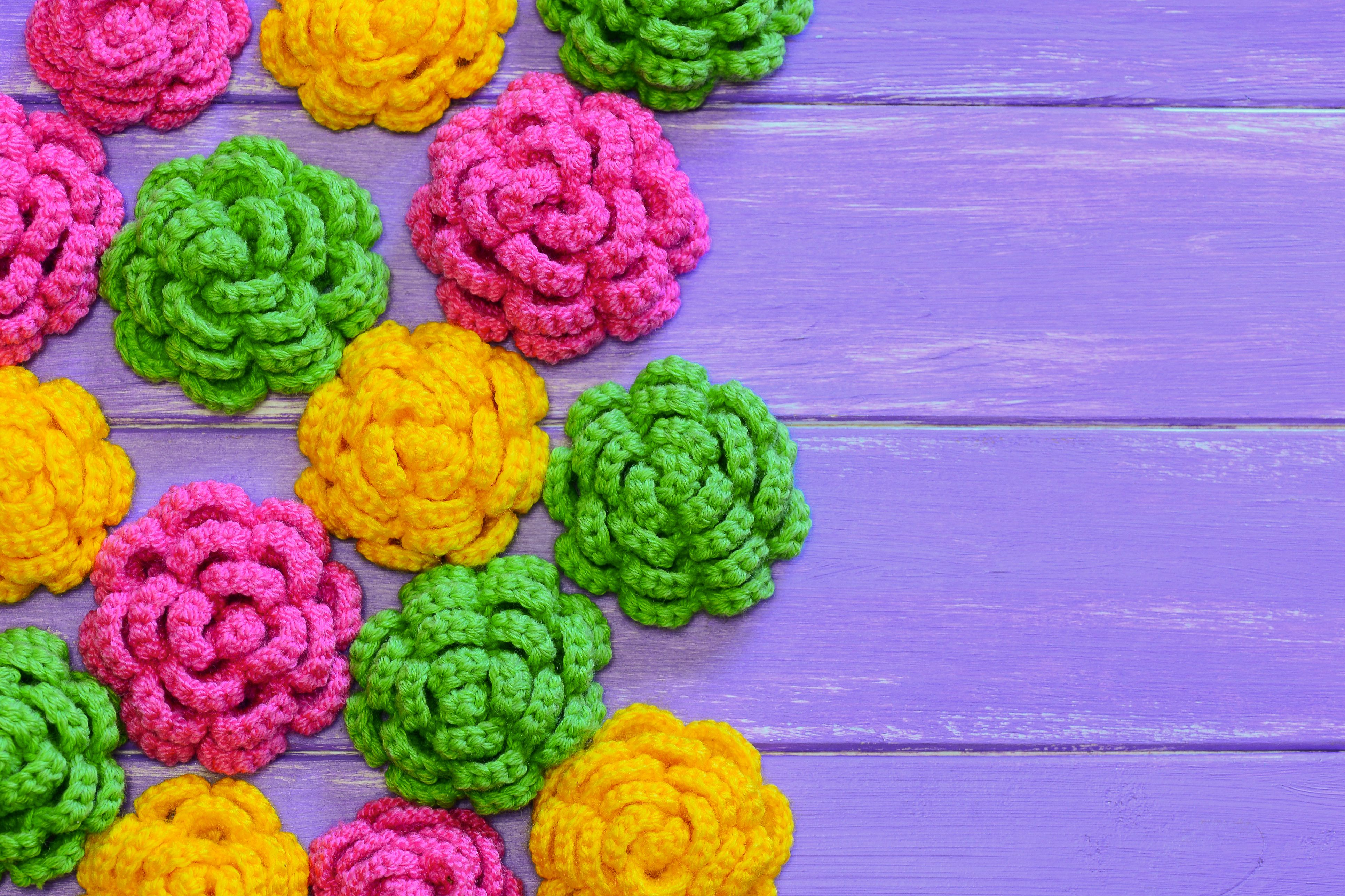 Crocheted flowers. Yellow, pink and green crocheted flowers. Multicolored floral ornaments. Bright background. Closeup