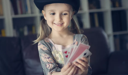little girl with playing cards