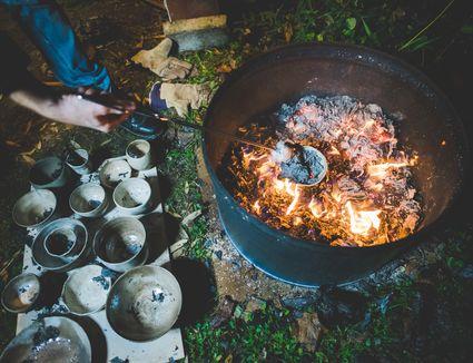 Raku pottery being fired outdoors at night