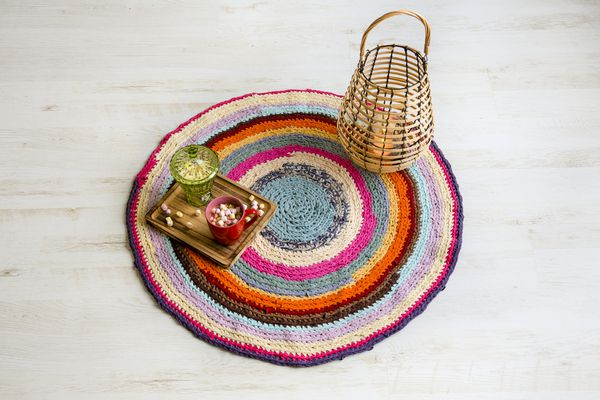 Colorful crochet rug from cut repurposed T-shirts on white wooden home floor with wood lantern, candle burning. Cup on hot chocolate wit marshmallows on tray. Flat lay view.