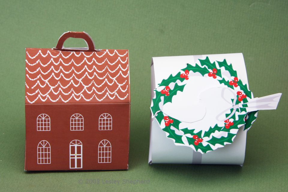 A printable miniature holly wreath topped box with silver ribbon and a gingerbread house shaped box