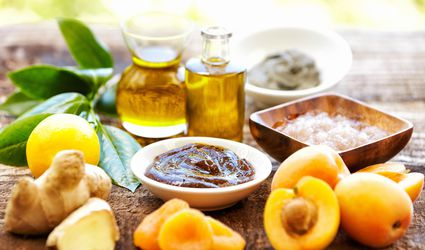Spa still life with organic scrub, massage oil, apricots, ginger