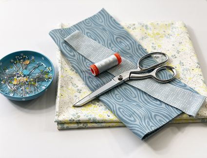 Fabric, scissors, thread, and pins on a table