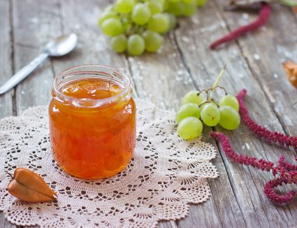 High Angle View Of Preserves In Jar By Grapes On Table At Home