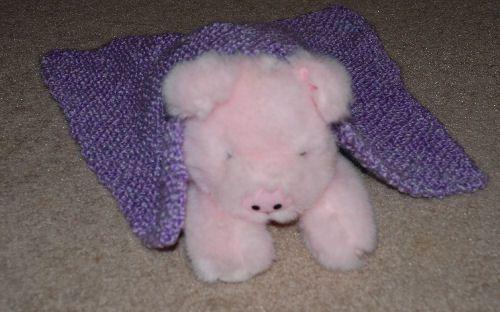 bias doll blanket on a stuffed pig sitting on carpet