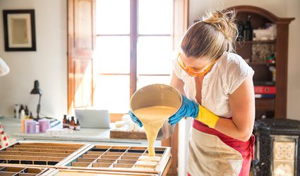 Young woman pouring liquid lavender soap into moulds in handmade soap workshop