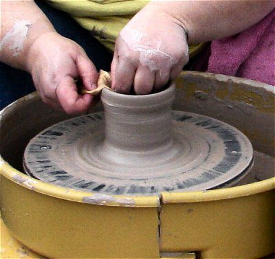 Compressing and smoothing the rim of formed pottery