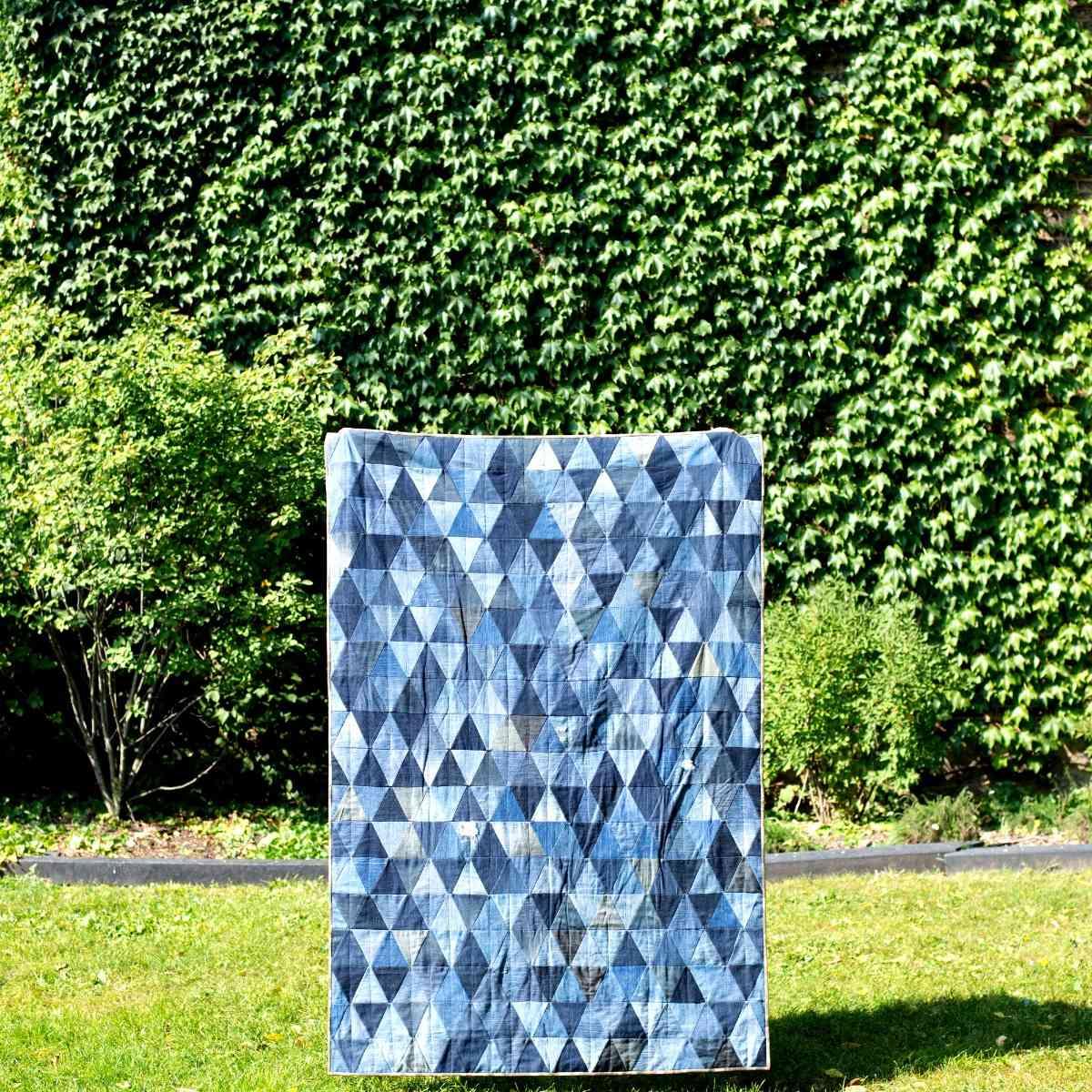 A blue denim quilt in a green yard