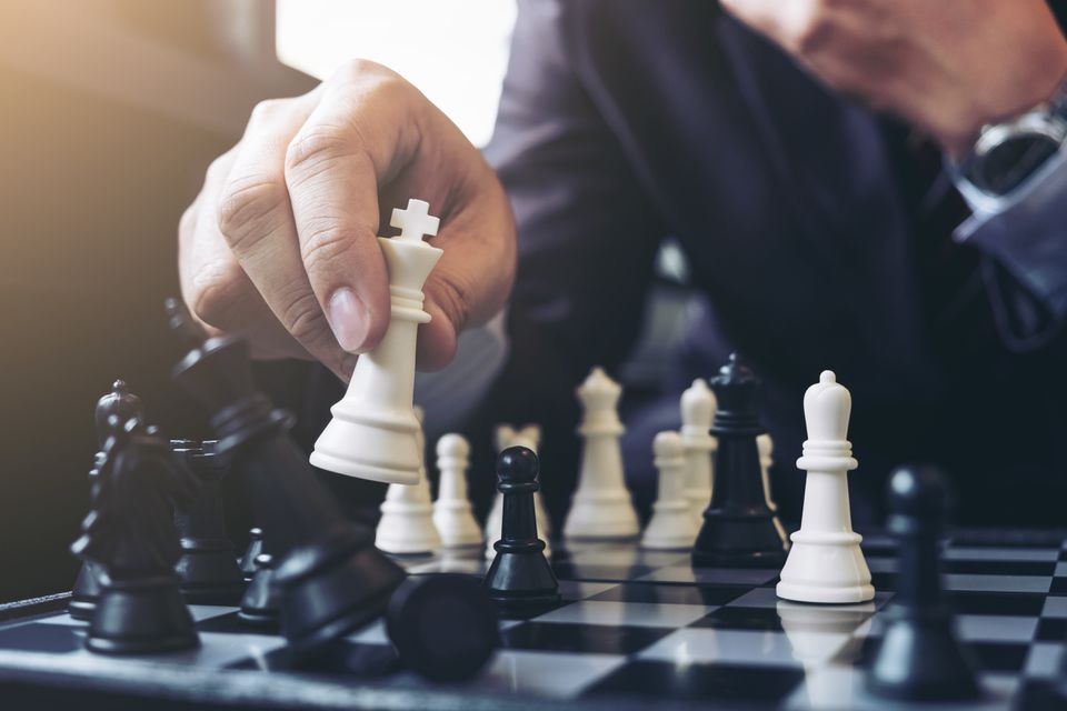 Midsection Of Businessman Playing Chess At Table