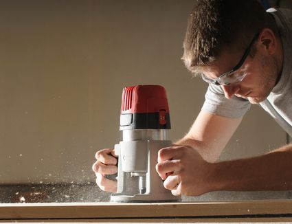 A man using a wood router
