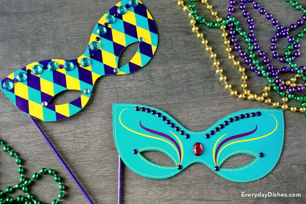 Two colorful Mardi Gras masks on a table with beads