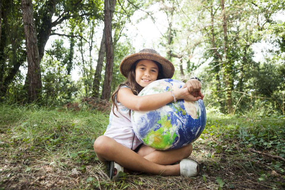 Little girl embracing world globe