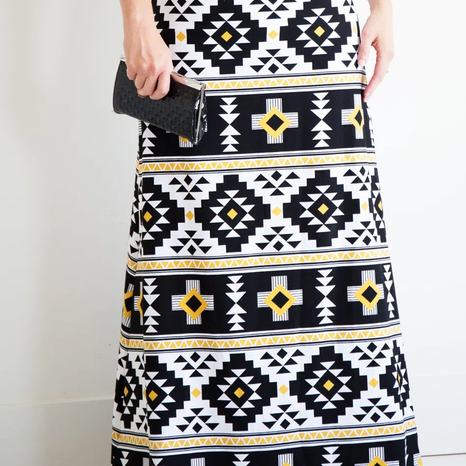 A woman wearing a black, yellow, and white maxi skirt