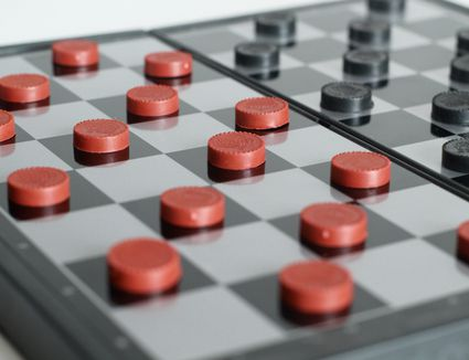 Close-Up Of Checkers Over White Background