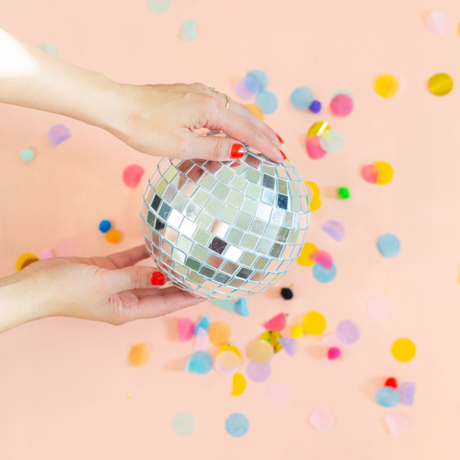 Hands holding a DIY disco ball on a pink background with confetti
