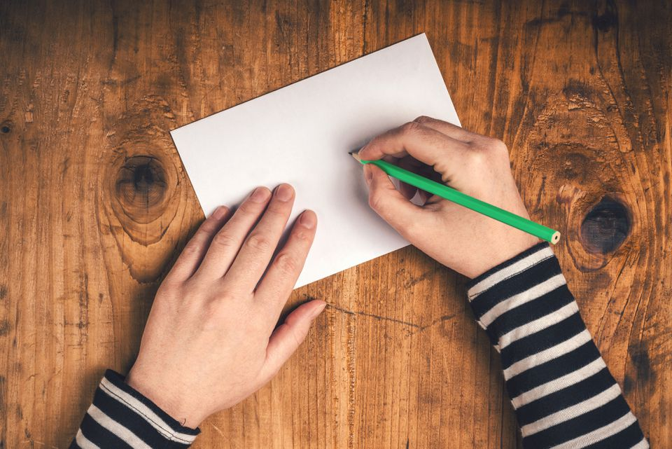 Woman writing recipient address on mailing envelope