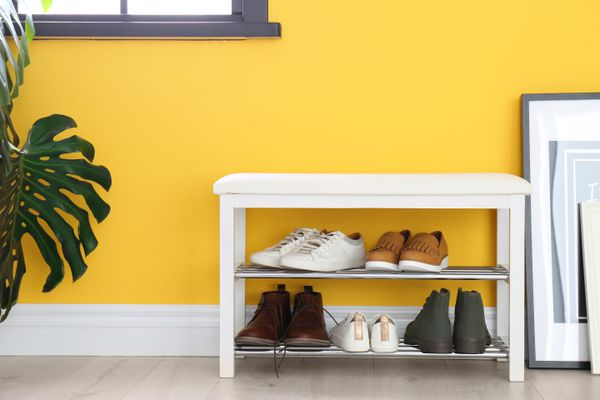 A shoe rack in front of a yellow wall