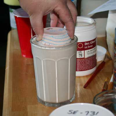 Pot being dipped into glaze, showing proper positioning.