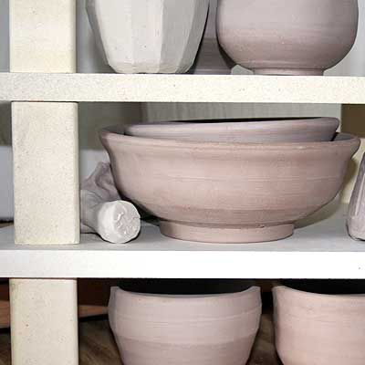Kiln furniture and pottery stacked for a bisque firing.