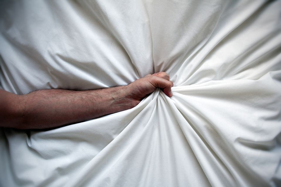 A hand clutching bedsheets