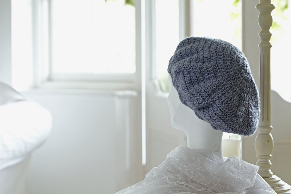 Grey crochet hat resting on a mannequin's head in a white bedroom.
