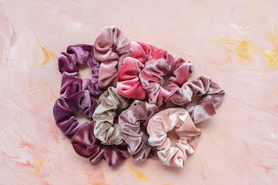 Collection of trendy velvet scrunchies on pink background