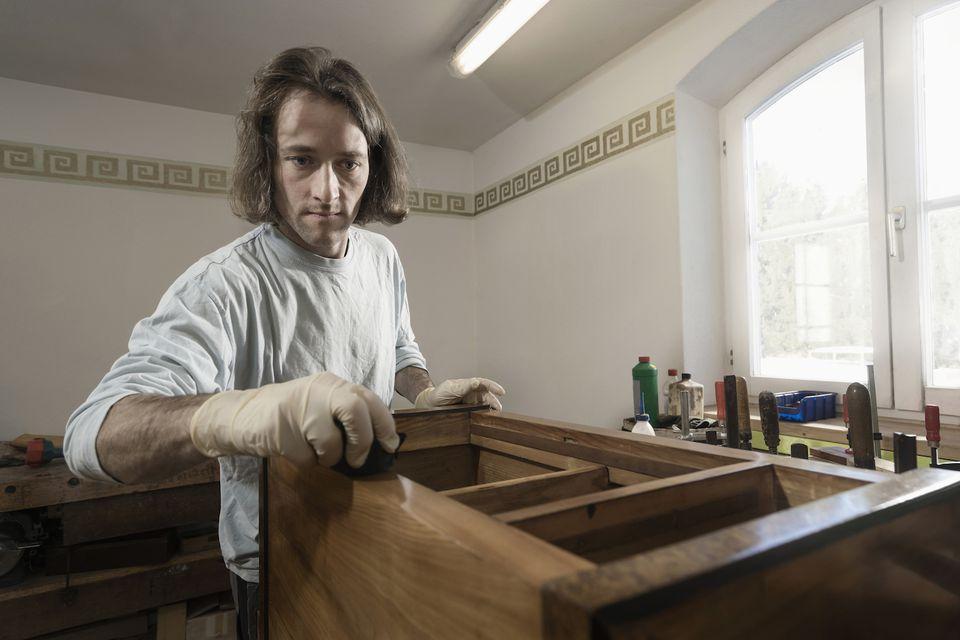 Carpenter French polishing on wooden drawer