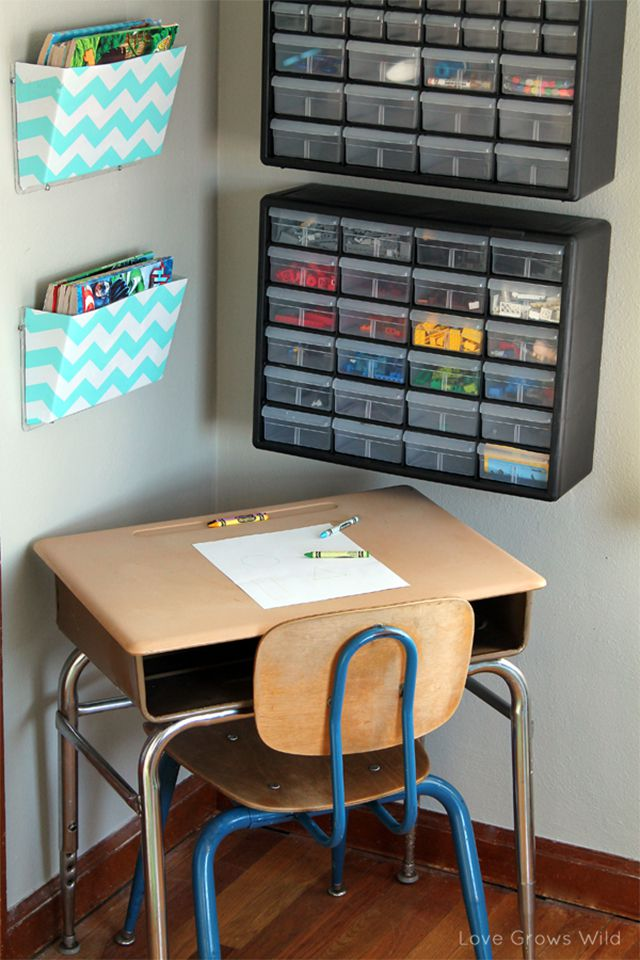 A children's desk with lego storage on the wall