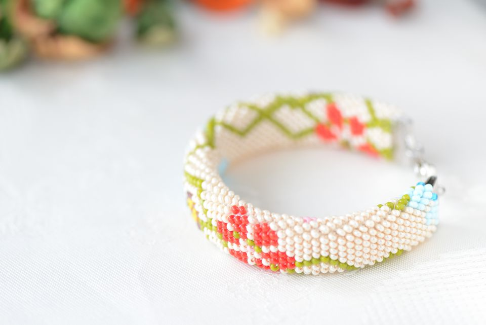 Bead crochet bracelet beige color with floral print close up