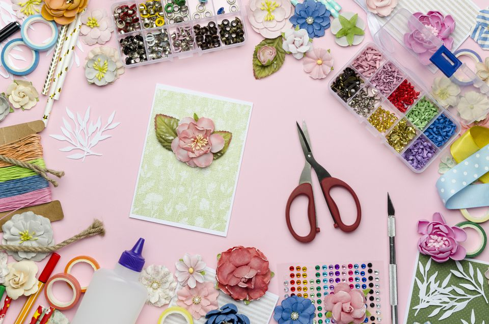 Paper flowers, scissors, homemade card, paper and scrapbooking items on pink background
