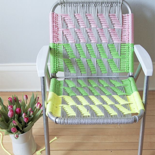A macrame lawn chair in pink, green, and yellow