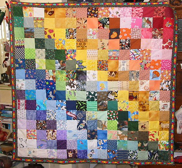 I Spy Quilt in rainbow colors hanging on a wall.