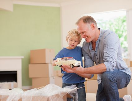 Father showing son model car in new house.