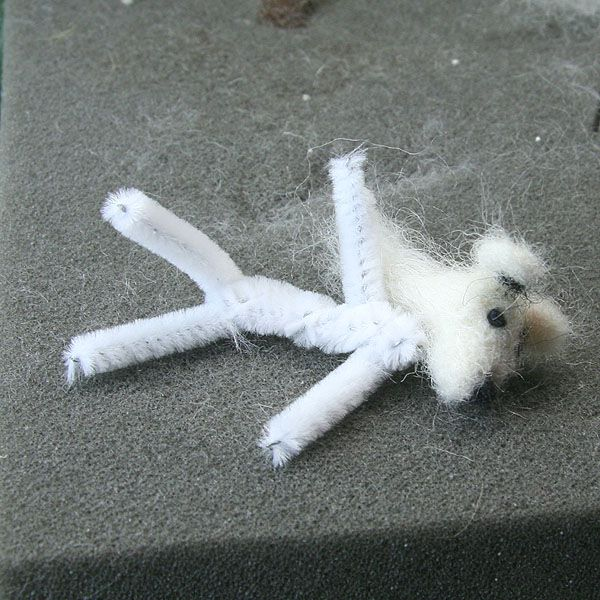 The felted head of a miniature dog in dollhouse scale, next to a body frame made from pipe cleaners