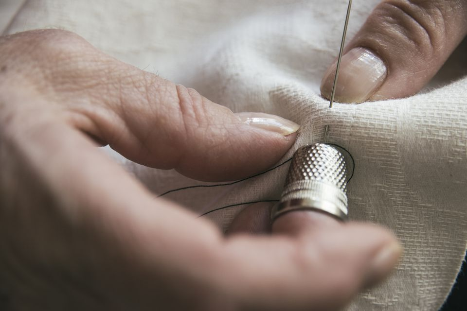person sewing with needle and thimble