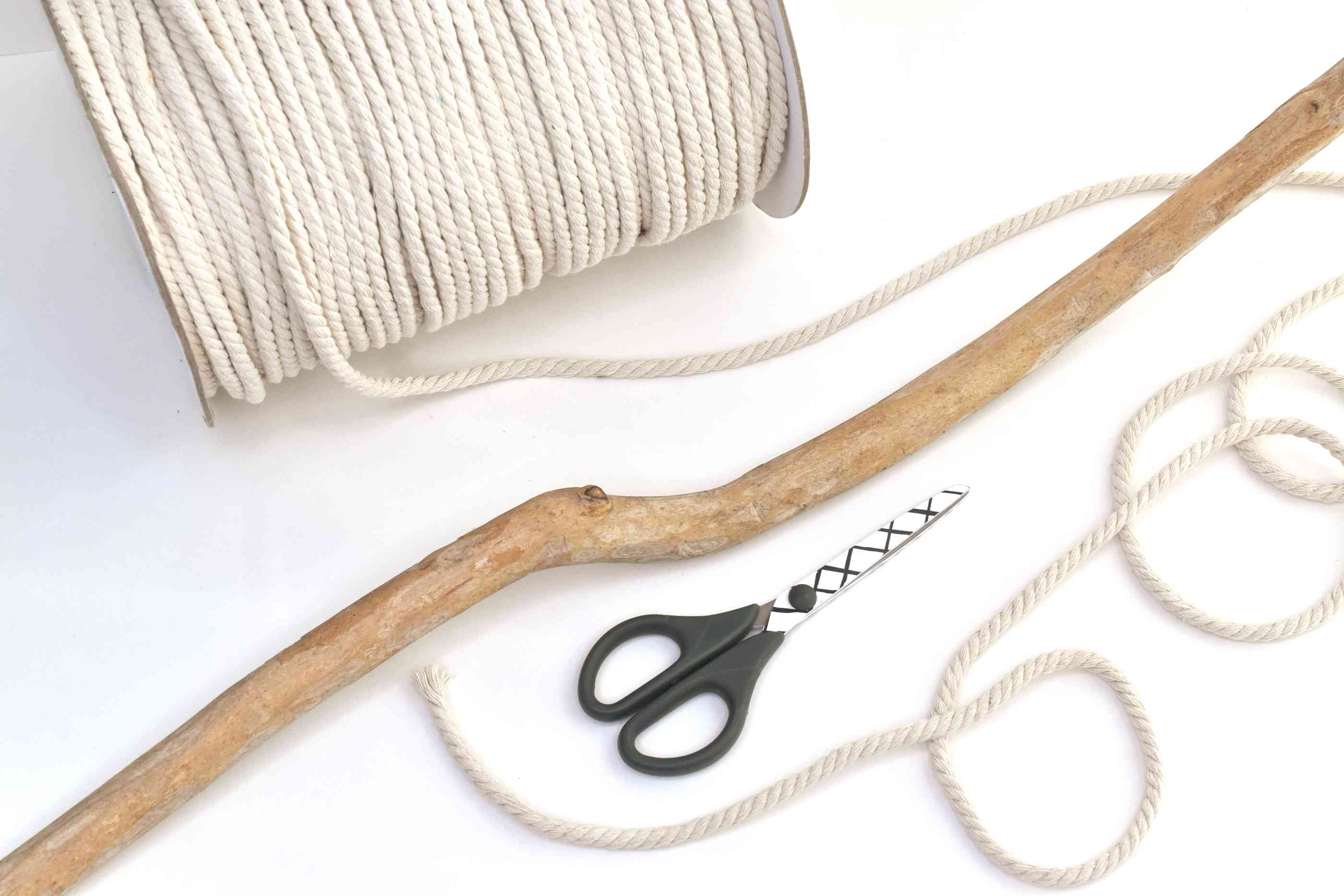 Supplies for making a macrame curtain with rope and a branch