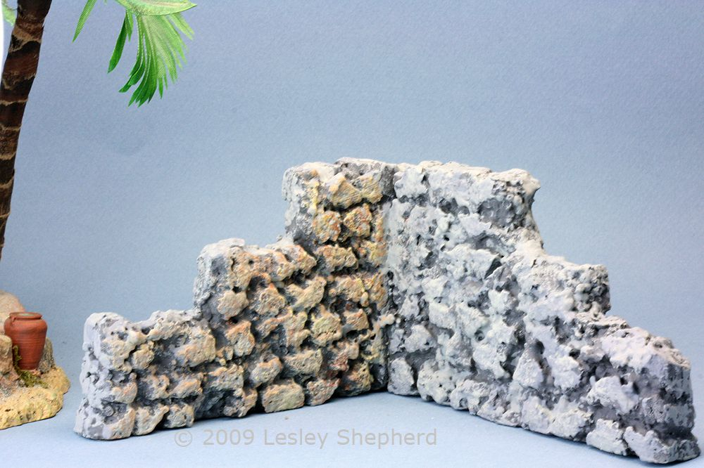A section of styrofoam faux stone wall colored to match existing resin miniatures.