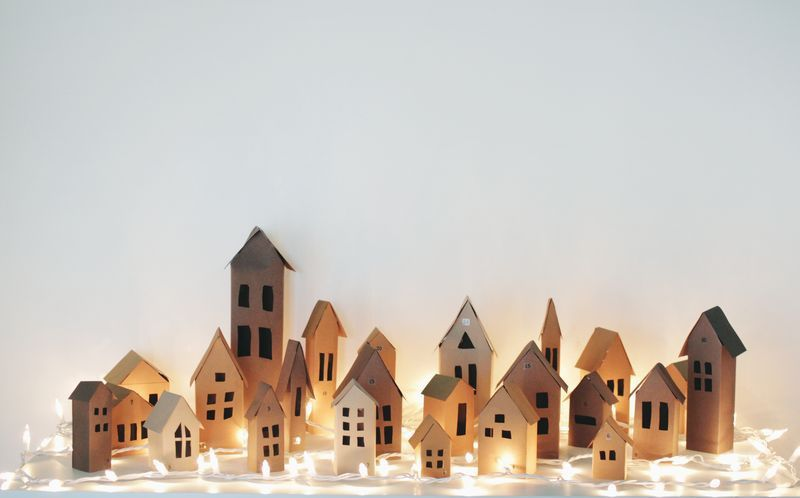 A village of houses made from paper lit up with white twinkly lights.