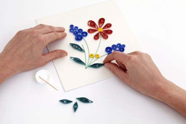 hands shaping a quilled design on a sheet of paper